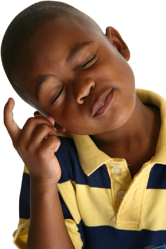 Adorable 5 year old African American boy against white background.
